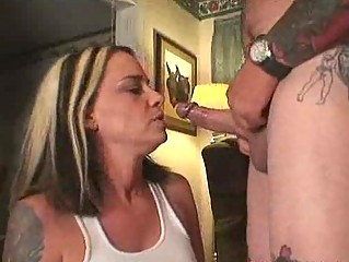 gorgeous milf sucking the dick of a tattooed man