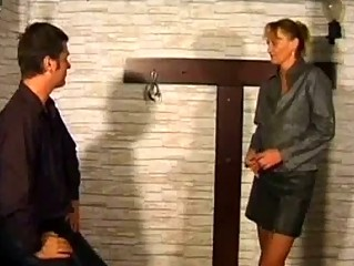 aged woman getting fastened to cross spanked with