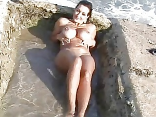 busty tanned milf in bikini doing striptease on